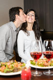 Couple dinner with love. Romantic anniversary dinner. Young playful couple having fun during the celebration. Man kissing cheerful woman Stock Photos