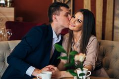 A couple dinners in a restaurant a man kisses a woman. A couple dinners in a restaurant a men kisses a woman,Romantic young couple at restaurant Stock Photography