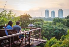 A couple dinning in front of the forest and the buildings. stock photography
