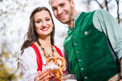 Couple in Dirndl and Tracht having Pretzel and Bier Royalty Free Stock Image