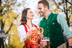 Couple in Dirndl and Tracht having Pretzel and Bier Royalty Free Stock Photography