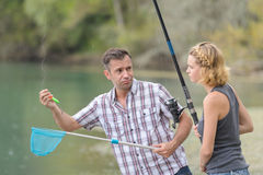 Couple disappointed that their fishing line empty. Couple disappointed that their fishing line is empty Stock Image