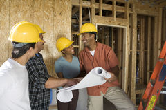 Couple Discussing Construction Plans With Contractors. Happy African American couple with contractors discussing plans of construction for their new house Royalty Free Stock Photo