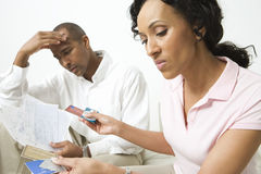 Couple Discussing Credit Card Bills. An angry African American couple with credit cards and bills Royalty Free Stock Photos