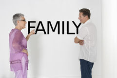 Couple discussing family issues against white wall with English text Stock Photos