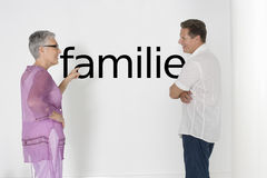 Couple discussing family issues against white wall with German text Familie Stock Photo