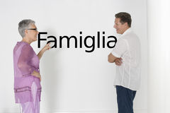 Couple discussing family issues against white wall with Italian text Famiglia Stock Photography
