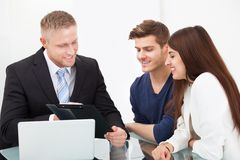 Couple discussing with financial advisor. Smiling young couple discussing with financial advisor at office desk Royalty Free Stock Photo