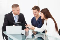 Couple discussing with financial advisor Stock Photos