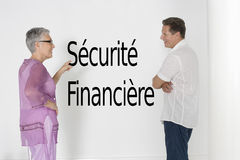 Couple discussing financial security against white wall with French text Sécurité Financière Stock Photos