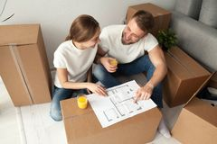 Couple discussing house plan sitting on floor with moving boxes. Happy couple discussing house plan looking at blueprint planning new home interior design, happy Royalty Free Stock Photo