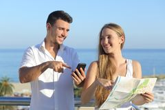 Couple discussing map or smartphone gps on vacations Stock Photos