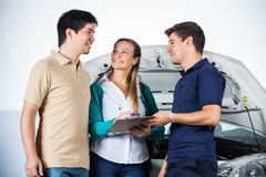 Couple Discussing With Mechanic While Signing Royalty Free Stock Photos