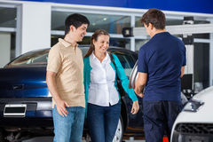 Couple Discussing Over Alloy With Mechanic Stock Photos
