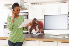 Couple Discussing Personal Finances In Kitchen. Young Couple Discussing Personal Finances In Modern Kitchen Royalty Free Stock Image
