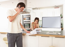 Couple Discussing Personal Finances In Kitchen Royalty Free Stock Photos