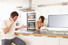 Couple Discussing Personal Finances In Kitchen Royalty Free Stock Images