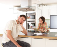 Couple Discussing Personal Finances In Kitchen stock images