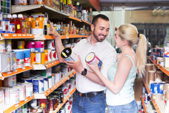 Couple discussing and selecting paint. Positive young couple discussing and selecting paint in the department Royalty Free Stock Images