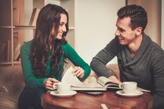 Couple discussing something in cafe. Couple with coffee and book discussing something in cafe Royalty Free Stock Image
