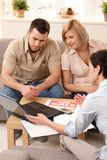 Couple in discussion with estate agent. Young couple listening to estate agent showing new house on laptop stock image