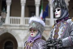 A couple disguised in elegant gray. One of the most beautiful carnivals in the world in the city, Venice, the most beautiful in the world Stock Photography