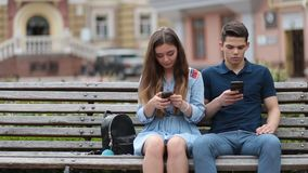Couple in disinterest moment with phones outdoors stock video