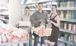 Couple displaying hopping basket with household goods. Positive  woman, men and boy displaying hopping basket with household goods in the shop Royalty Free Stock Images