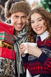 Couple With Disposable Cups And Christmas Presents Stock Image