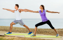 Couple do exercises on beach by ocean at daytime Stock Images