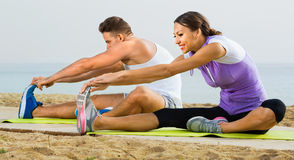 Couple do exercises on beach by ocean at daytime Stock Photo
