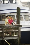 Couple at dock looking at each other. Royalty Free Stock Photography