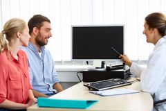 Couple and doctor pointing at computer at clinic Royalty Free Stock Photos
