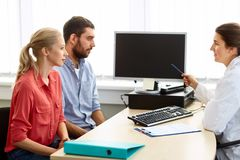 Couple and doctor pointing at computer at clinic Stock Images