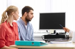 Couple and doctor pointing at computer at clinic Stock Image