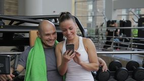 The couple does posts with selfies in the social network while standing in the gym. The woman in white top holds her smartphone and touch the screen by her stock video