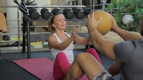 The couple does sit-ups on the pink mats during the training in the modern gym. The man and woman is in front of and transfer the orange ball to each other on stock footage