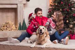 Couple with dog at christmastime. Smiling young couple playing with dog in antlers at christmastime at home royalty free stock photo