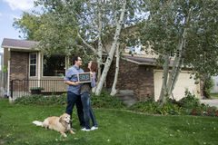 Couple and dog family in front of new home holding sold blackboard sign and keys Stock Photo