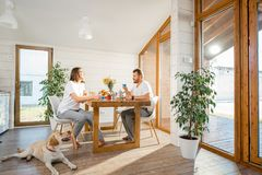 Couple with dog in the house. Young couple having a breakfast sitting with dog in the dining room in the wooden country house stock photo