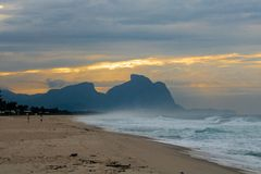 Couple and dog running on the beach of Barra da Tijuca in a beautiful dawn with the stone of Gavea in the background - Rio de Jane stock photography