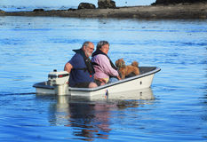 Couple with dog on small boat. A closeup of an older couple wearing glasses and life jackets on the water running a small outboard motor with a small dog in the Royalty Free Stock Images