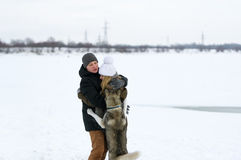 Couple and dog standing on the snow. Stock Photos