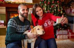Couple with dog taking selfie on Christmas holydays Stock Photo