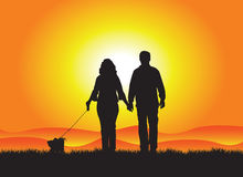 Couple dog walking. In the sunset Royalty Free Stock Photo