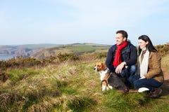 Couple With Dog Walking Along Coastal Path Royalty Free Stock Photos