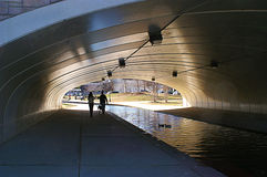 Couple with Dog Walking Under Tunnel Royalty Free Stock Photo