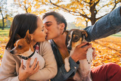 Couple with dogs making selfie while kissing in autumn park