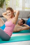 Couple doing abdominal crunch. Young couple doing abdominal crunch lying on fitness mat at home in living room Royalty Free Stock Photos