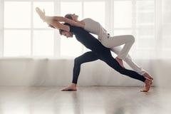 Couple doing acro-yoga. Fit young couple doing acro-yoga in modern studio royalty free stock image